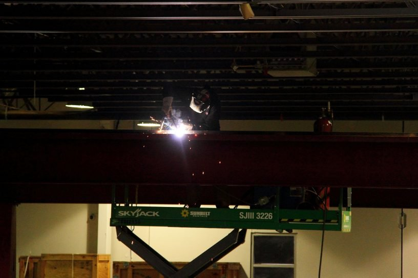 A man on a crane welding a steel beam.